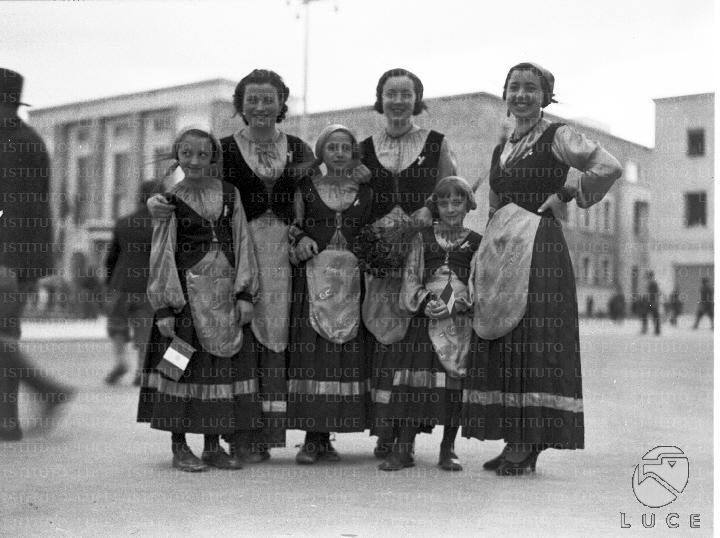 Ragazze e bambine posano in una piazza di Littoria, vestite in abiti tradizionali data 26.04.1936